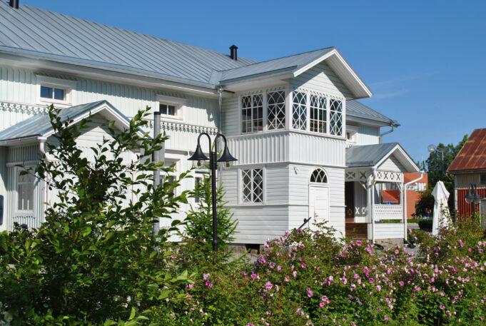 Kesäinen kuva. Valkoinen puinen rakennus, sininen taivas, etuviistoon kuvattuna, ruusuaidan takaa kuvattuna